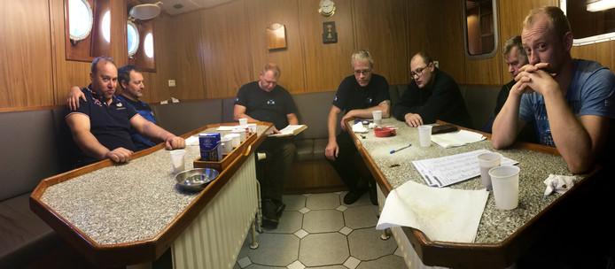 De zeven bemanningsleden van de PZ 657. Schipper Jan de Boer (derde van links) leest voor uit de Bijbel. Die is net als het psalmenboek vast onderdeel van de inventaris.