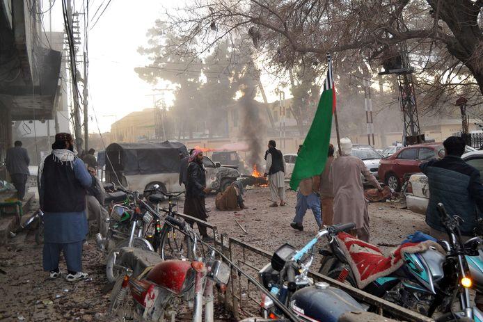 Mensen staan te midden van het puin na de explosie in het Pakistaanse Quetta.