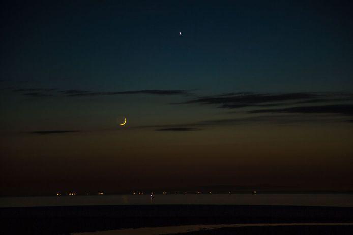 De maan en Venus boven het strand van Kijkduin