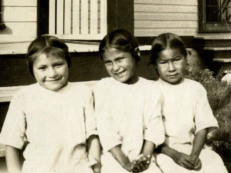 Een historische foto uit 1900 van drie kleine meisjes op hun eerste schooldag op de Little Pine Indian School in Little Pine, Northwest Territories, nu Saskatchewan, Canada.  Beeld Provincial Archives of Saskatchewan / EPA