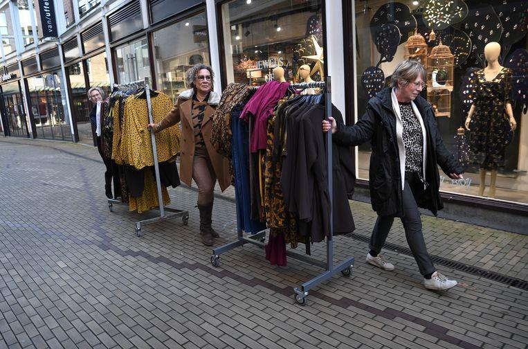 Een damesmodezaak verhuist wat kleding in  Amersfoort De lockdown zorgt er voor dat alle niet-essentiële winkels hun deuren moeten sluiten. Beeld Marcel van den Bergh / de Volkskrant