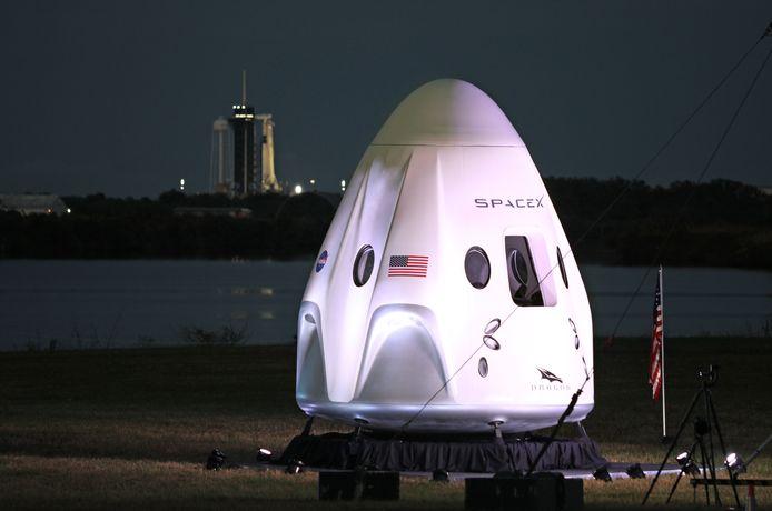 Een levensgroot model van de Crew-1 spacecraft module, terwijl op de achtergrond de SpaceX-raket klaarstaat voor de lancering.