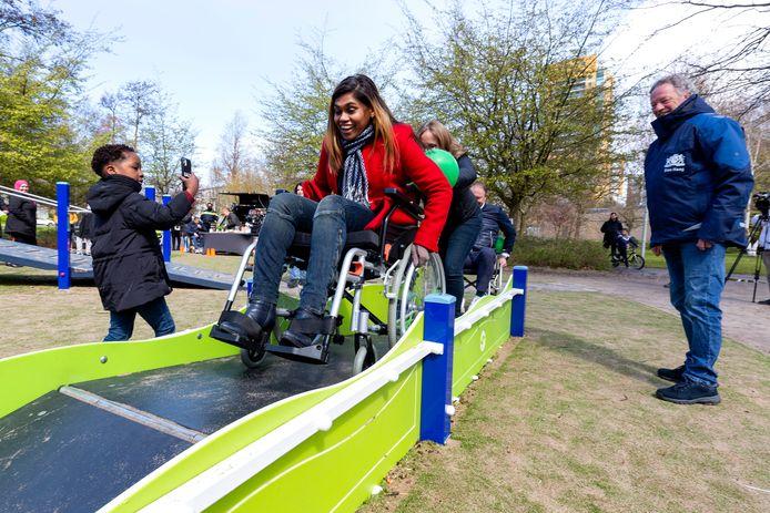Wethouder Kavita Parbhudayal legt in een rolstoel het bijzondere speelparcours af in de totaal vernieuwde inclusieve speelplaats Melis Stokepark.