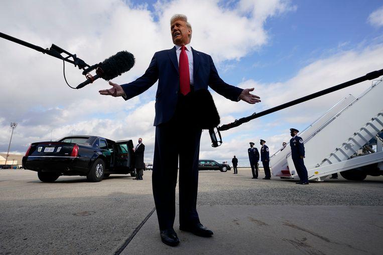 President Donald Trump staat zaterdag de pers te woord bij zijn presidentiële vliegtuig, de AIr Force One, voordat hij vertrekt om campagne te gaan voeren in Pennsylvania. Beeld AP