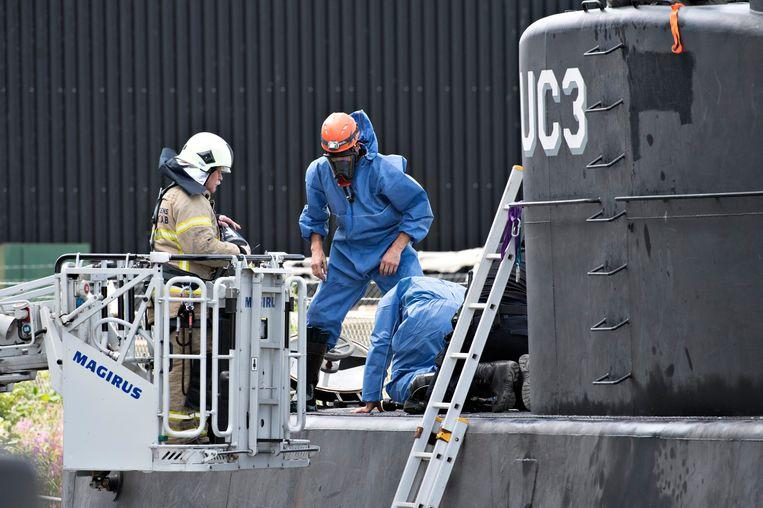 Technici van de politie doorzoeken de geborgen duikboot. Beeld epa