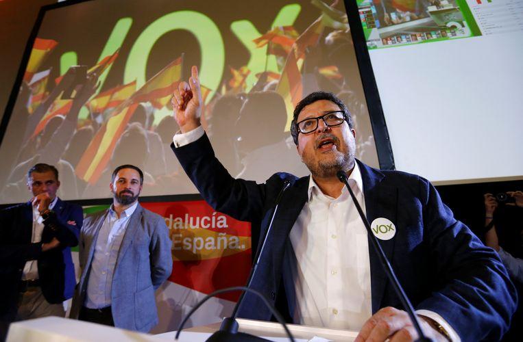 Vox-lid Francisco Serrano speecht na de verkiezingsuitslag bij de regionale verkiezingen, Vox-leider Santiago Abascal kijkt links toe.  Beeld REUTERS