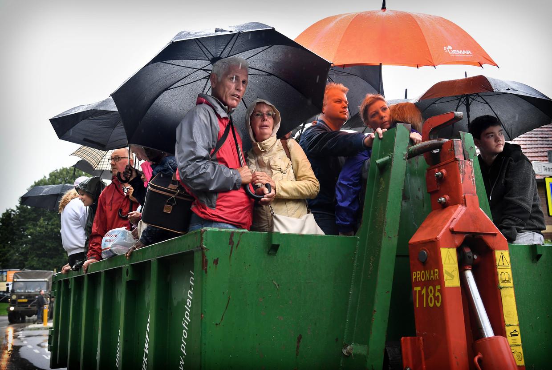 Inwoners van het overstroomde Valkenburg worden met behulp van een landbouwvoertuig geëvacueerd.  Beeld Marcel van den Bergh / de Volkskrant