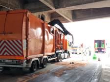 Auto's onder de olie nadat vrachtwagen tegen onderkant van brug botst