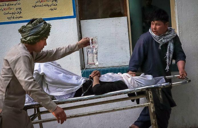 Een van de gewond geraakte meisjes wordt een ziekenhuis in Kaboel binnen gedragen.