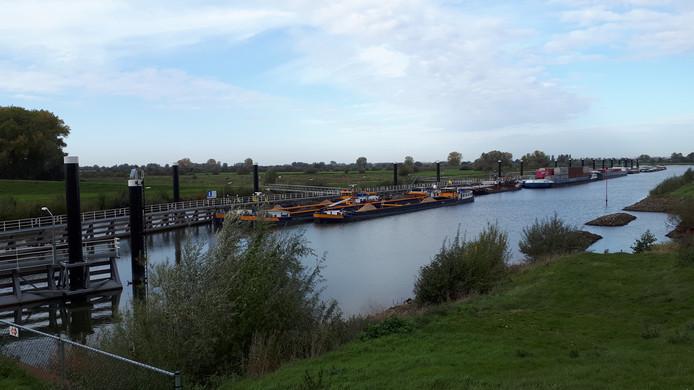 Binnenvaartschepen liggen vast voor de sluis bij Empel.