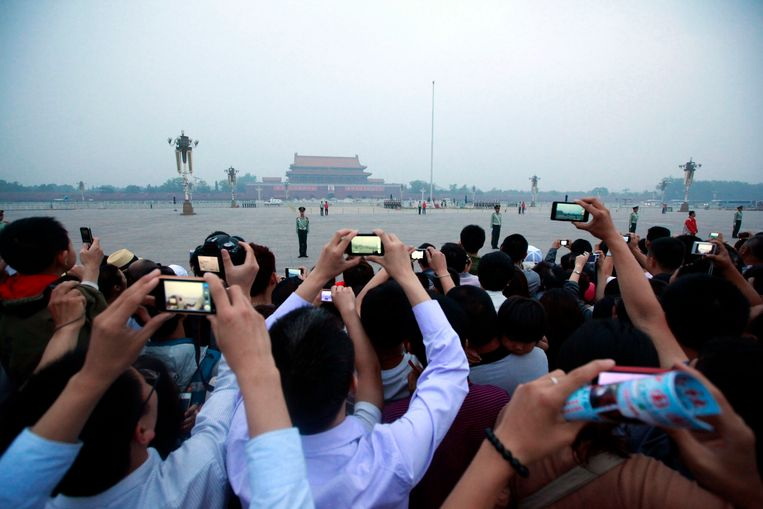 Tourists take photos of the flag raising ceremony on Tiananmen Square as they gather to mark the anniversary of the deadly 1989 crackdown on pro-democracy protestors, in Beijing, China, Monday, June 4, 2012.  (AP Photo/Ng Han Guan) Beeld null