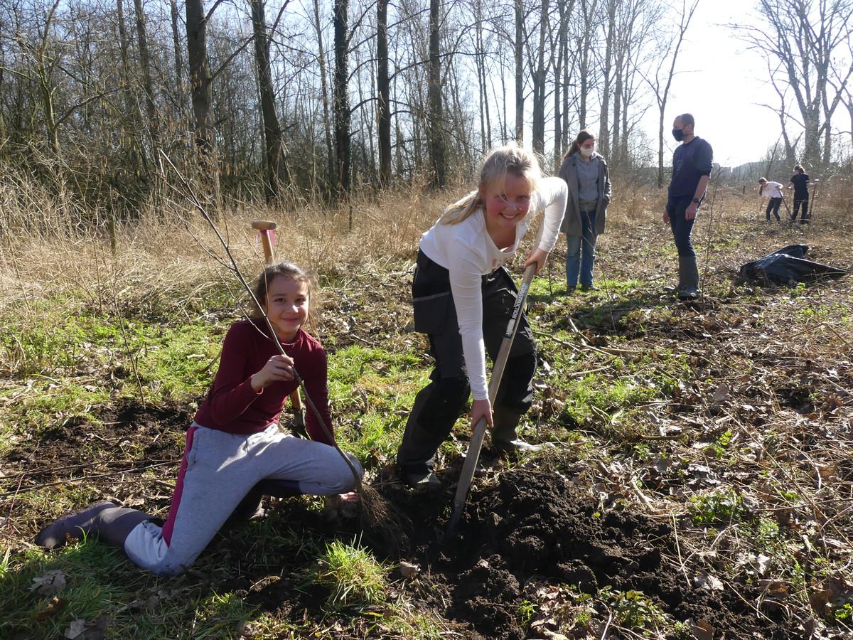 Vienna Krul en Camille Dhaenens steken een boom in de grond.