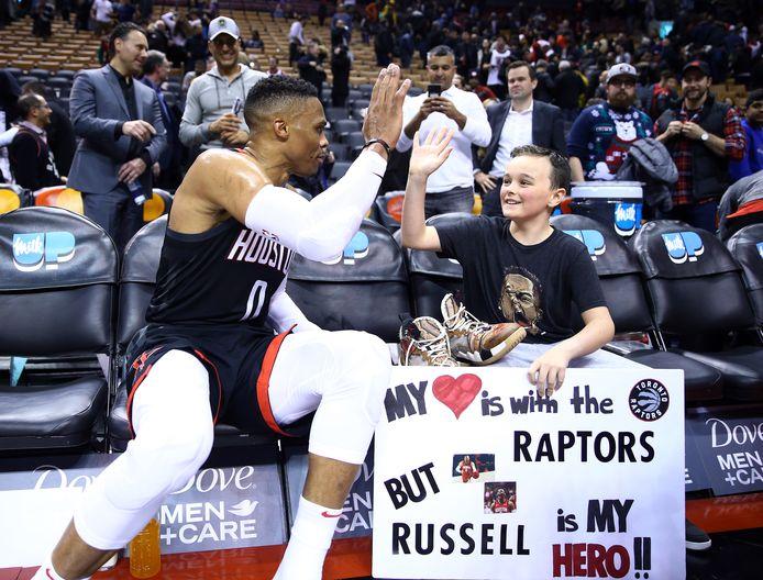 Russell Westbrook geeft een jonge fan zijn schoenen.
