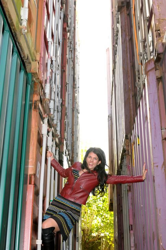 Kristel Groenenboom poseert tussen de containers van haar bedrijf.