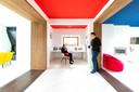 De leefruimte vormt een geheel, maar door de gekleurde plafonds en houten kaders wordt ze gevoelsmatig verdeeld in verschillende hoekjes.