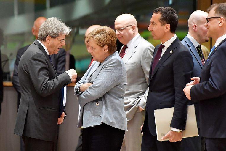 De Italiaanse premier Paolo Gentiloni bespreekt iets met de Duitse bondskanselier Angela Merkel. De Oostenrijkse kanselier Christian Kern kijkt toe. Beeld AP