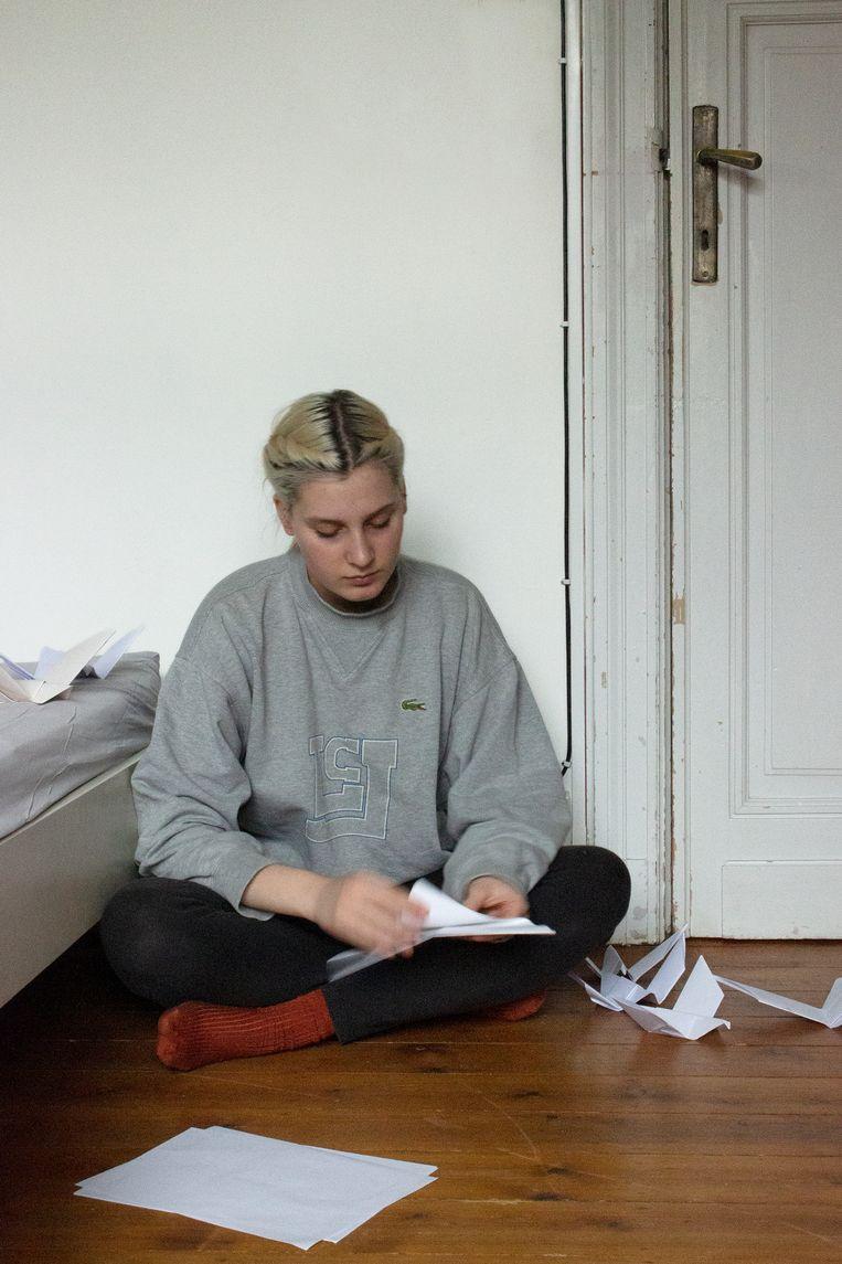 Flora Vanclooster vouwt papieren vogeltjes, een verwijzing naar de totem van Frederik bij de scouts: vermakende salangaan. Beeld Flora Vanclooster