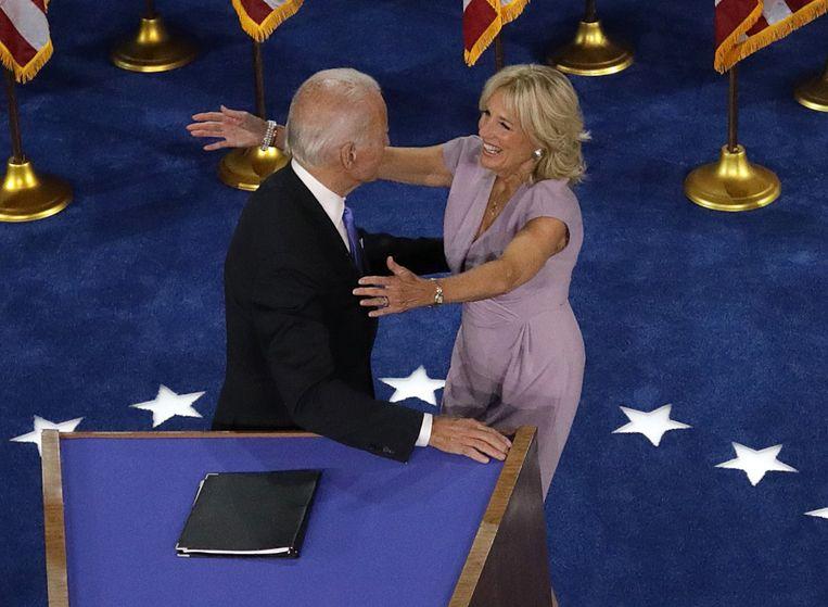 De Democratische presidentskandidaat Joe Biden omhelst zijn vrouw Jill na zijn acceptatiespeech op de laatste avond van de vrijwel volledig 'virtuele' Democratische Conventie in Wilmington (Delaware). Beeld Getty Images