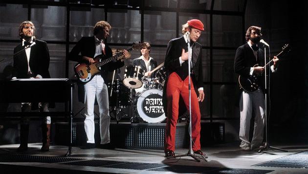 Drukwerk, met rode pet zanger Harry Slinger.