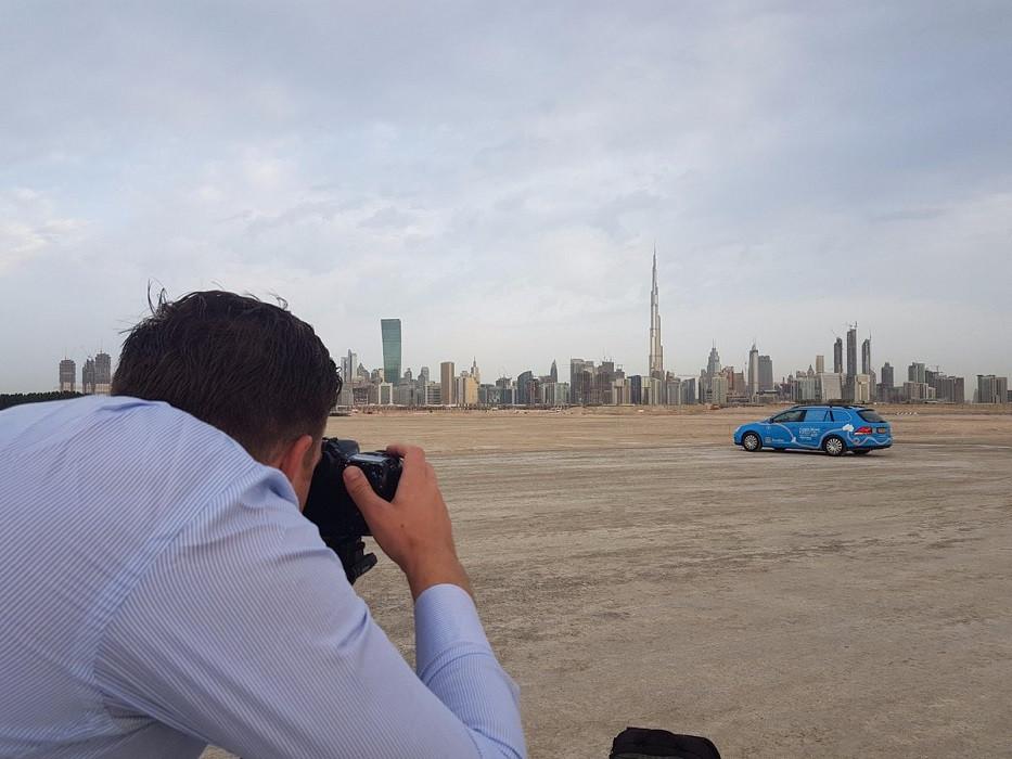 Wiebe Wakker fotografeert zijn wagen met op de achtergrond de skyline van Dubai.
