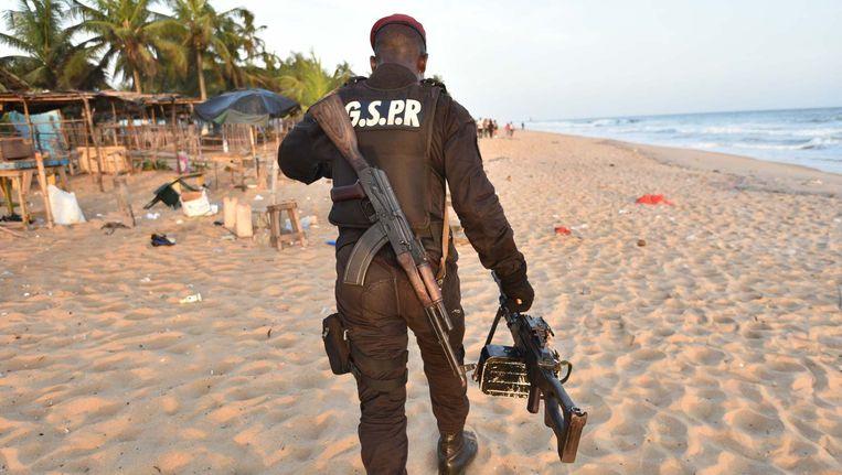 Een soldaat op het strand in Ivoorkust, na de aanslag op een resort op 13 maart. Beeld Afp