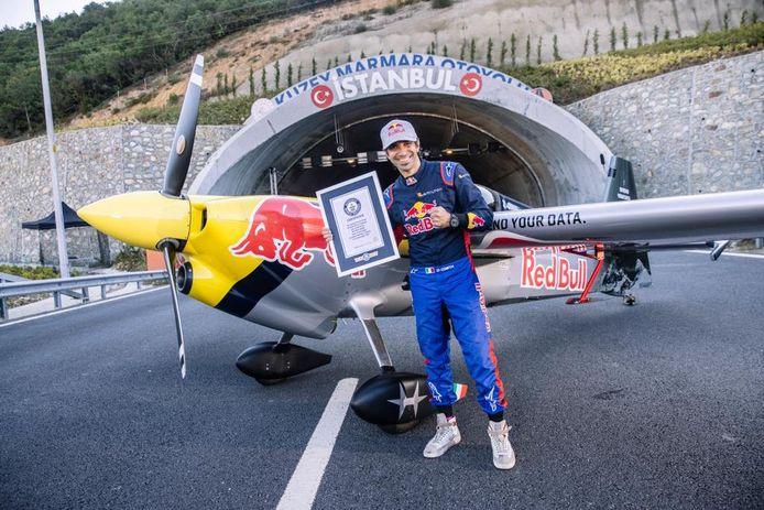 Dario Costa pose devant son avion avec son certificat Guiness.