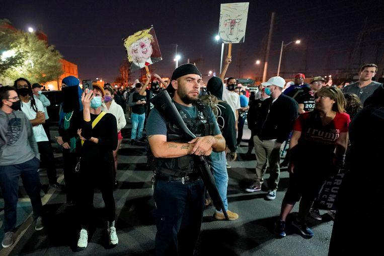 Een zwaargewapende man protesteert aan een stembureau in Phoenix. Beeld AP