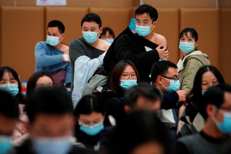 Mensen staan op een vaccinatie locatie nadat ze een dosis van een coronavirusvaccin (COVID-19) hebben gekregen tijdens een door de overheid georganiseerd bezoek in Shanghai, China Beeld REUTERS