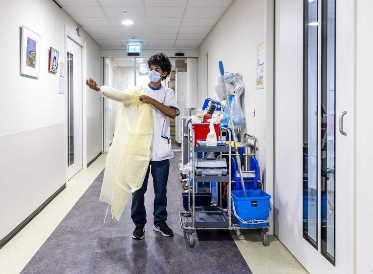 Een medewerker van de schoonmaakploeg trek beschermende kleding aan in het Westeinde-ziekenhuis in Den Haag.  Beeld Remko de Waal / ANP