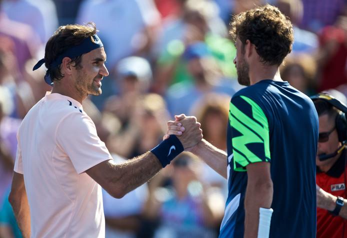 Roger Federer krijgt de felicitaties van Robin Haase.