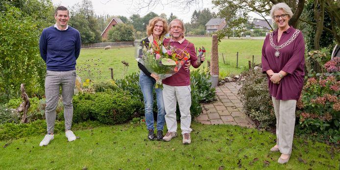 Jan en Roos Bosch (midden) hebben de Beste Buur Bokaal in de gemeente Wierden gewonnen en kregen de prijs van burgemeester Tigchelaar (r).