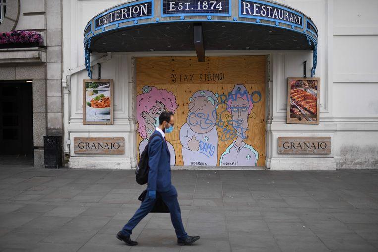 Een man wandelt voorbij een gesloten restaurant in het centrum van Londen. Beeld AFP