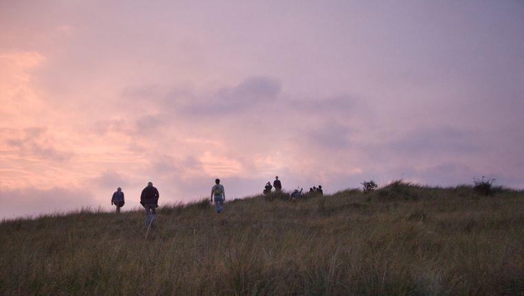 De duinen vormen het decor van ITGWO, de ondergaande zon verzorgt een spectaculaire lichtshow. Beeld Io Cooman