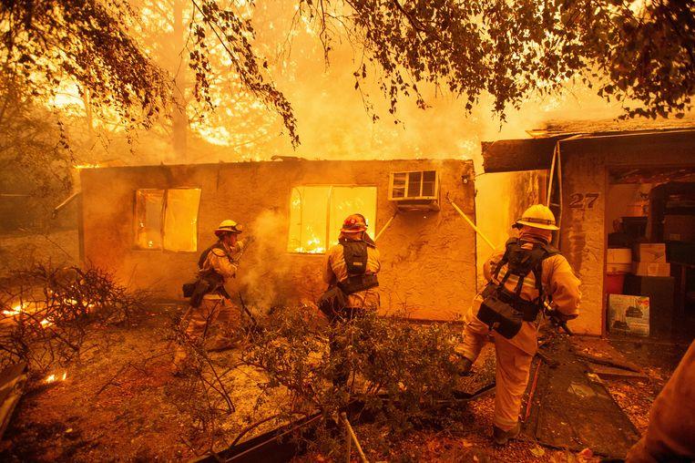 Paradise, 9 november 2018: brandweerlieden halen een muur omver in hun gevecht met de vuurzee. Beeld Hollandse Hoogte / AFP
