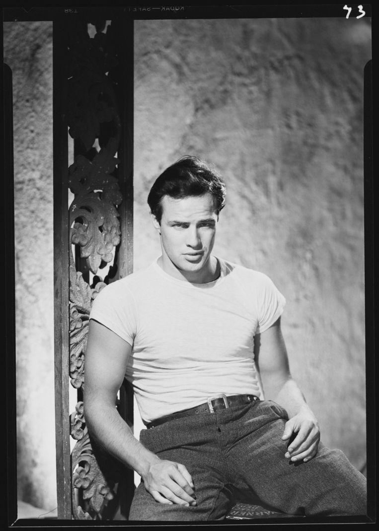 Brando met het legendarische witte T-shirt, en de jeansbroek die zo vaak gewassen was dat zijn genitaliën zich erin aftekenden als 'een veelbelovend zakje lekkers'. Beeld Getty Images
