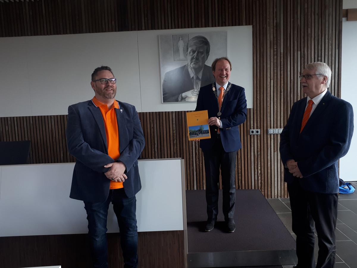 Voorzitter Kees Schilten  van de stixchting Koningsfeesten Zwijndrecht (links) en historicus Kees Popijus overhandigden het eerste exemplaar aan burgemeester Hein van der Loo