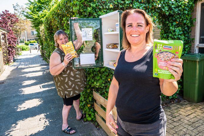 Frannie Potter (l) en Barbara Snabel beheren een buurt voedselkast, waarin buurtbewoners houdbare levensmiddelen kunnen delen.