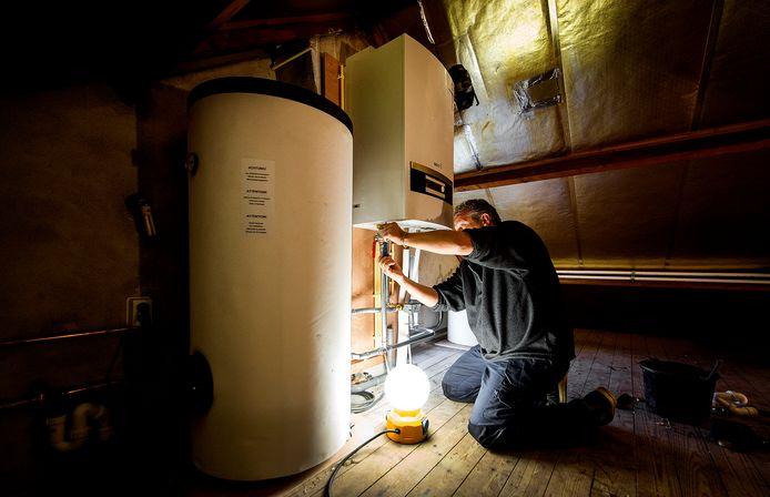 Een installateur is bezig met de installatie van een cv-ketel.