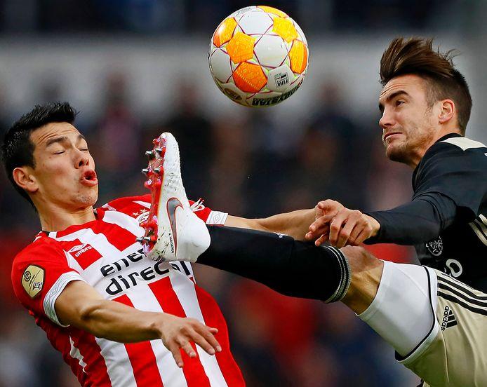 Beeld uit het duel tussen PSV en Ajax (3-0) eerder dit seizoen: Hirving Lozano schrikt van het hoog geheven been van Nicólas Tagliafico.