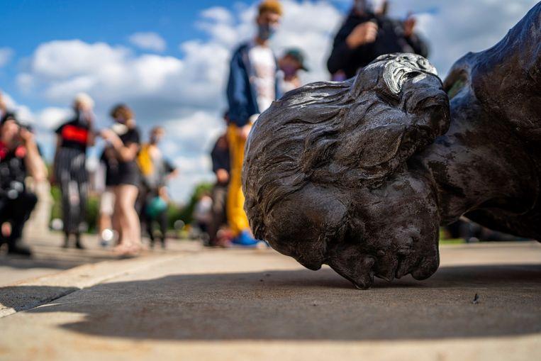 Actievoerders staan naast een neergehaald standbeeld van Christoffel Columbus in Minnesota. Beeld AP