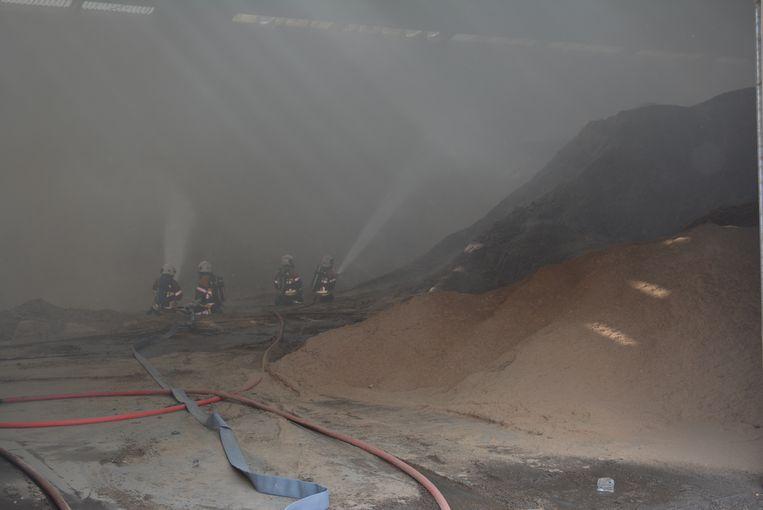 De brandweerlui blussen 3.000 ton houtstof in de loods aan de Kortemarkstraat (links).