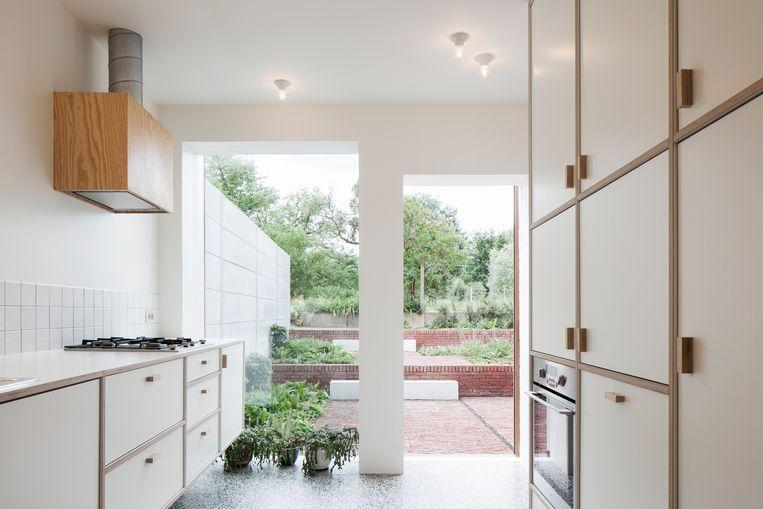 In de keuken valt het daglicht royaal binnen door de hoge ramen, de zwevende keukenkastjes zijn op maat gemaakt. Beeld Johnny Umans