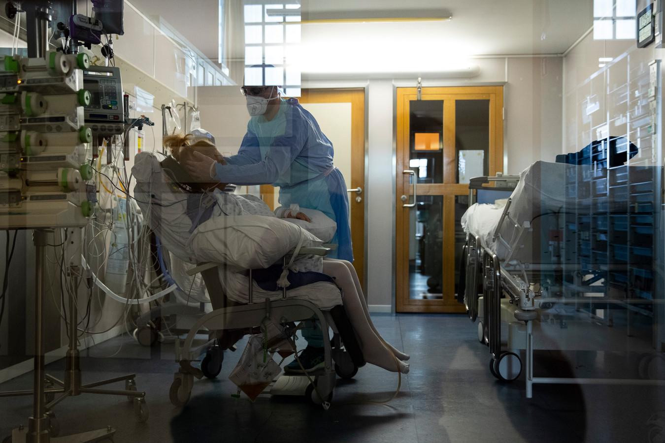 Een zorgmedewerker met een coronapatiënt op de afdeling intensieve zorgen van het CHU-ziekenhuis in Luik.