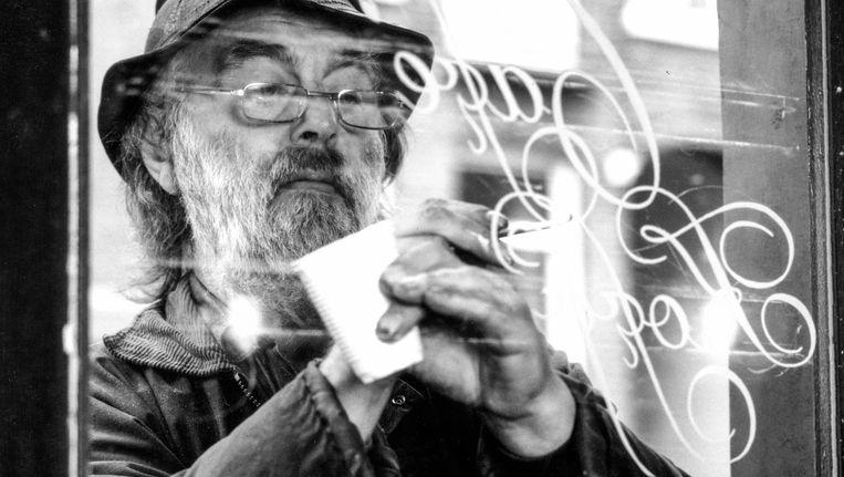 Leo Beukeboom aan het werk met zijn karakteristieke krulletters op een Amsterdams café Beeld Tom Grijzenhout