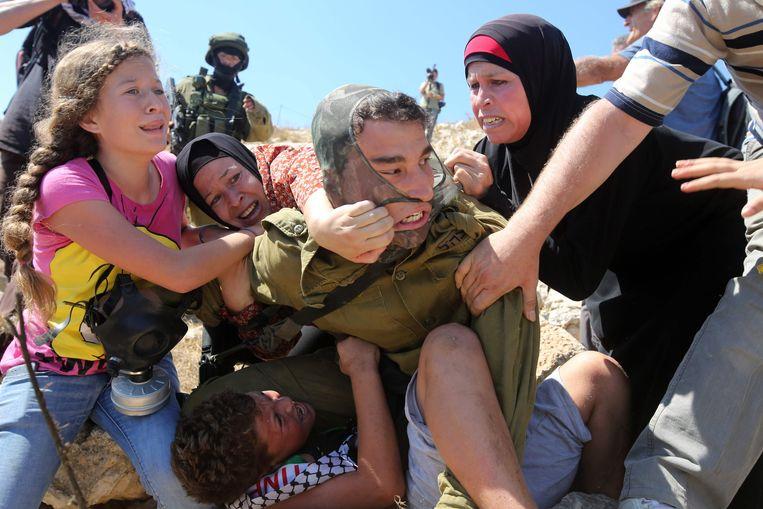 Op deze foto uit 2015 probeert Ahed Tamimi (links) met familieleden een Palestijnse jongen (onder) te bevrijden, terwijl die wordt vastgehouden door een Israëlische soldaat. Beeld AFP