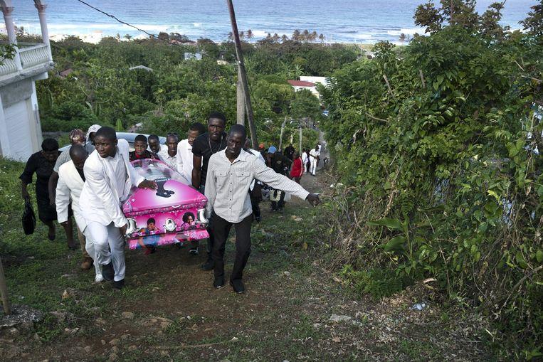 De begrafenis van Pauline Burke-Frazer in May Pen, Jamaica. Vuurwapens spelen zo'n belangrijke rol bij de moorden op Jamaica dat de autoriteiten een lijst hebben gemaakt van de 30 dodelijkste wapens. (Tyler Hicks/The New York Times) Beeld NYT