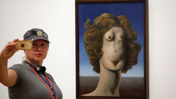 Een bezoeker neemt een foto met een schilderij van Magritte tijdens een eerdere expo in New York.