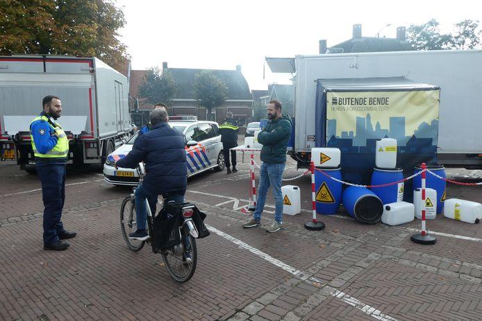 Een voorbij fietsende bezoeker in gesprek met een boa over drugscriminaliteit.