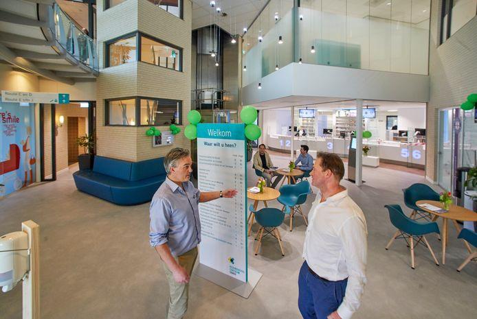 Huisarts Loek van Cruchten (rechts) in gesprek met apotheker Joeri Beek in de centrale hal van gezondheidscentrum Ceres. Op de achtergrond de eigenaren van het gebouw: Sjon Reijers (links) en Roel van Bakel.