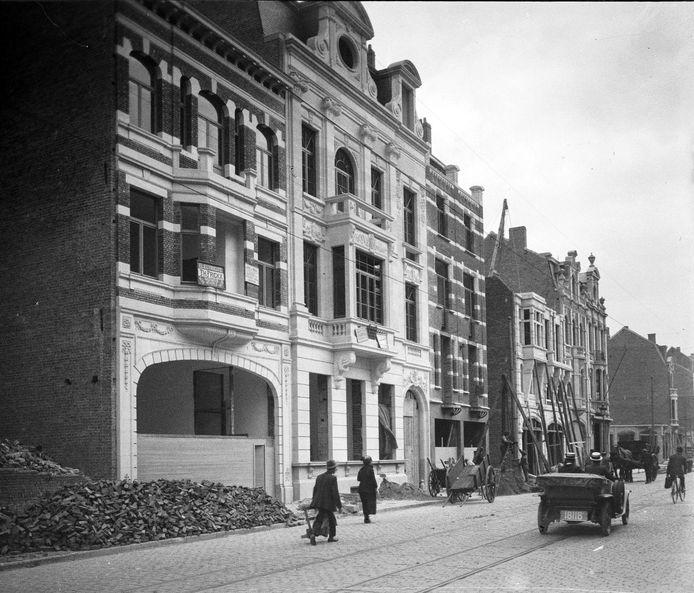 Een beeld van de wederopbouw van Leuven na de 'Groote Oorlog'. Een pand is niet meer dan een hoop bakstenen, terwijl andere al in de steigers staan.